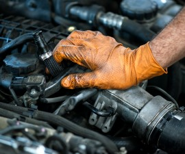 Hand of a mechanic on a car engine