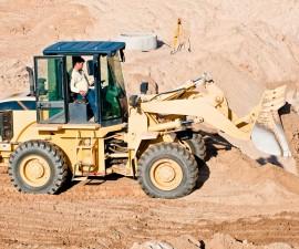 11740914_l-Wheel loader excavator unloading sand during earthmoving works at construction site
