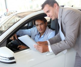 10624717 - car seller with car buyer looking at electronic tablet
