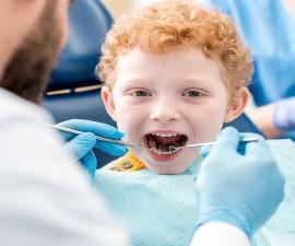 Dentist examinating boy's teeth